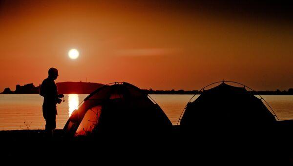Отдыхающие в палатках на берегу Азовского моря в окрестностях поселка Курортное