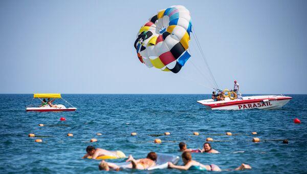 Отдыхающие купаются и катаются на парашюте в Судаке, Крым