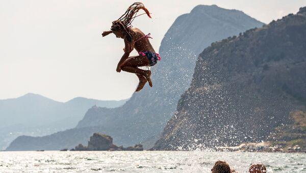 Отдыхающие купаются в Черном море в Судаке, Крым