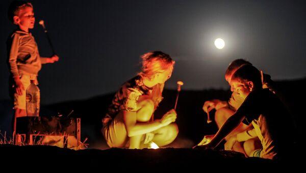 Туристы во время полного лунного затмения над мысом Меганом в Крыму