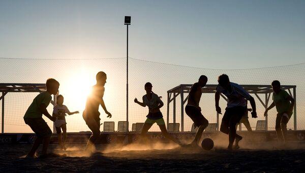 Отдыхающие на пляже играют в футбол в поселке Оленевка, Крым