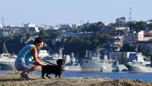 Женщина с собакой в бухте в Севастополе