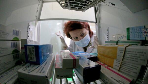 Фармацевт выбирает лекарства в аптеке. Архивное фото