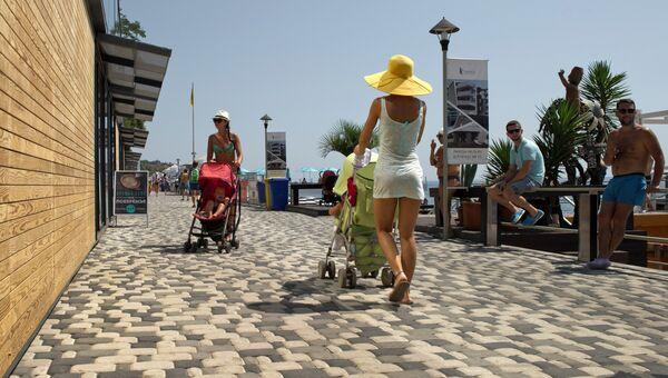 Мамы с колясками гуляют на набережной вдоль Массандровского пляжа в Ялте