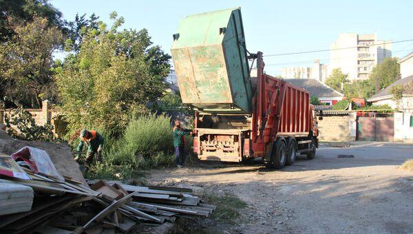 Сотрудники МУП Экоград за работой на одной из мусорных площадок в Симферополе