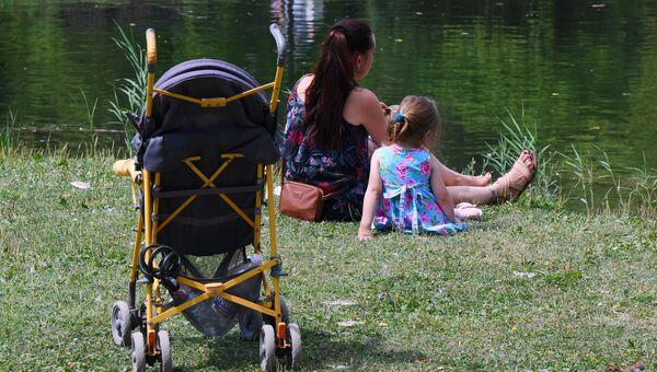 Женщина с ребенком отдыхают возле озера в парке им. Гагарина в Симферополе
