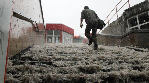 Мужчина поднимается по лестнице подземного пешеходного перехода в Симферополе во время сильного ливня