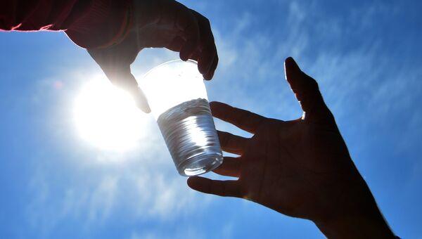 Участнику Казанского марафона 2016 - Проверь себя в Казани передают стакан воды на пункте питания