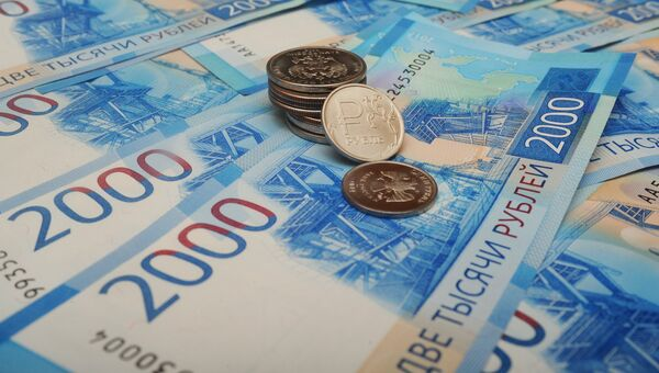 Банкноты номиналом 2000 рублей и монета 1 рубль с графическим обозначением символа рубля