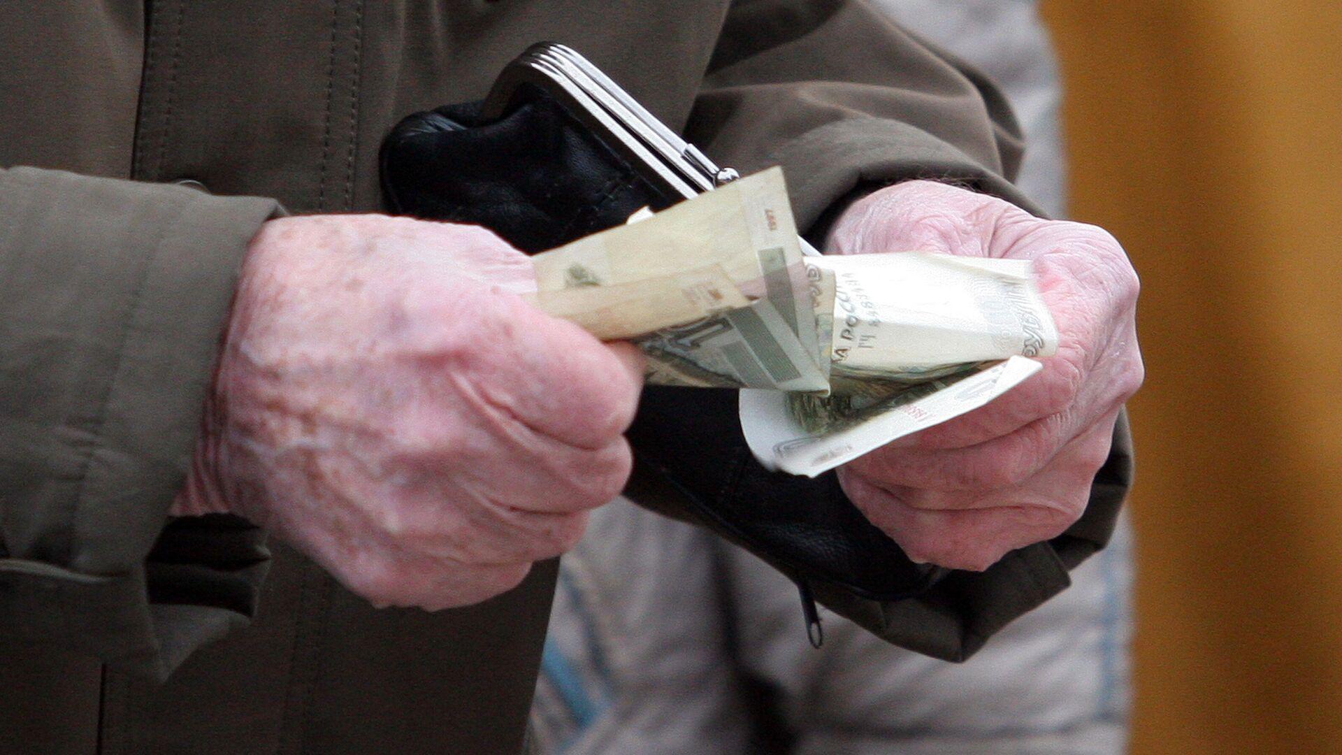 Пенсионер держит в руках кошелек и деньги - РИА Новости, 1920, 12.09.2021