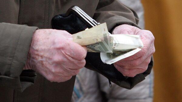 Пенсионер держит в руках кошелек и деньги