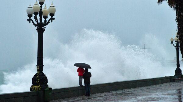Люди на набережной Ялты во время шторма на Черном море