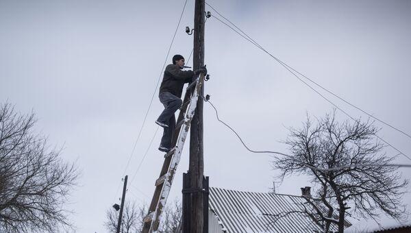 Мужчина ремонтирует линию электропередач