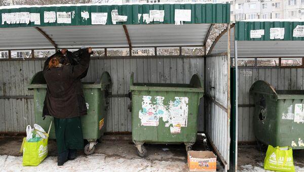 Женщина роется в мусорных контейнерах в Симферополе