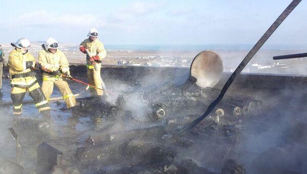 Сотрудники МЧС тушат пожар на месте взрыва газовых баллонов на крыше девятиэтажного дома в Щелкино