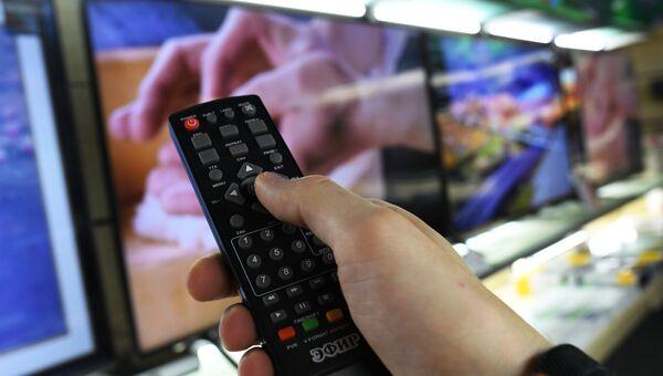 Мужчина пользуется пультом от приставки для приема цифрового телевизионного сигнала