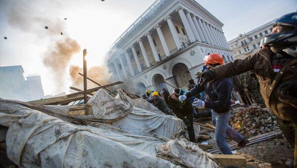 Сторонники оппозиции кидают камни на площади Независимости в Киеве, где начались столкновения митингующих и сотрудников правопорядка