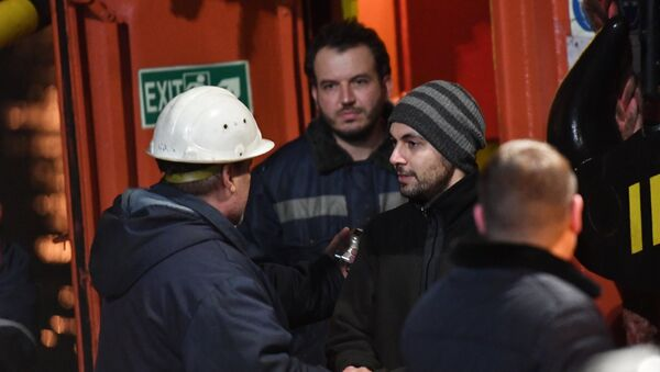 Иностранный моряк (справа), спасенный с одного из горящих танкеров, покидает буксир морской спасательной службы Меркурий в торговом порту Керчи. 22 января 2019
