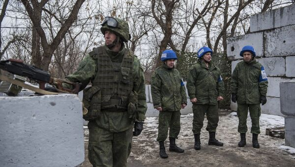 Военнослужащий ЛНР и наблюдатели ОБСЕ на контрольно-пропускном пункте в районе Станицы Луганской