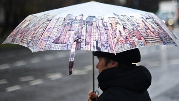 Женщина под зонтом во время дождя