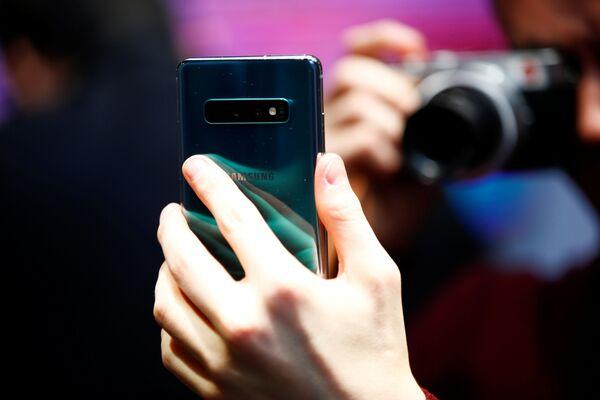 Журналист фотографирует новый Samsung Galaxy S10e  на презентации в Лондоне