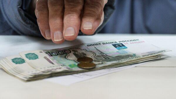 Пенсионер получает пенсию в одном из отделений Почты России