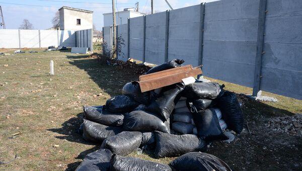 Забор и строительный мусор, ограждающий земельный участок, засаженный краснокнижной крымской сосной у парка Обелиска Памяти в Севастополе