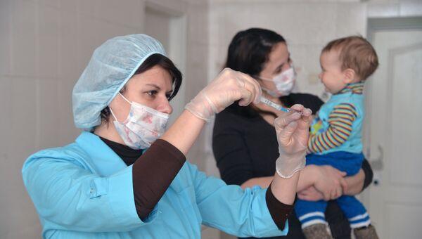 Медсестра готовит шприц для прививки ребенку. Архивное фото
