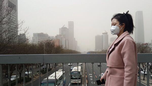 Жительница Пекина в защитной маске во время смога. Архивное фото
