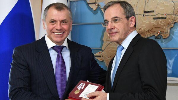 Председатель Госсовета Республики Крым Владимир Константинов (слева) вручает депутату Национального собрания Франции Тьерри Мариани медаль за позицию по признанию Крыма неотъемлемой частью РФ
