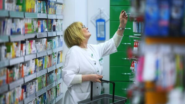 Фармацевт раскладывает лекарственные препараты в одной из аптек. Архивное фото
