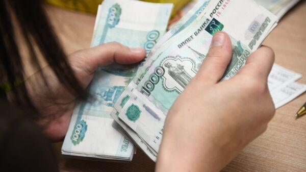 Женщина пересчитывает рубли