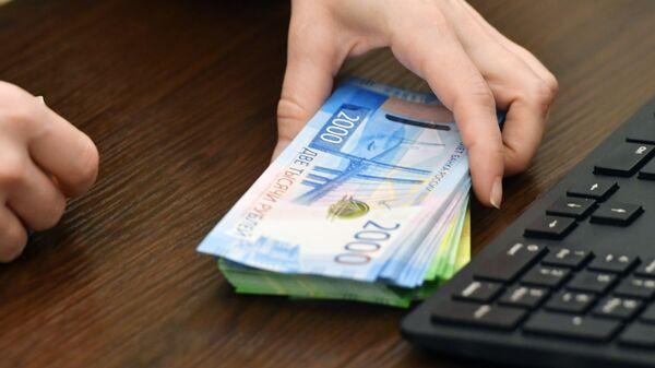 Сотрудница банка проводит денежные операции с новыми купюрами номиналом 200 и 2000 рублей
