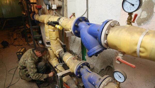 Сантехник красит трубу на тепловом узле в подвале одного из жилых домов