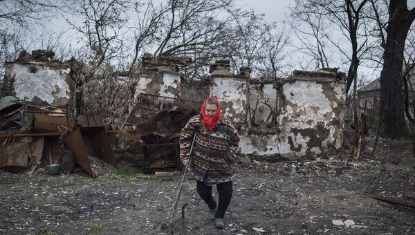 Женщина у разрушенного дома в поселке Саханка Донецкой области