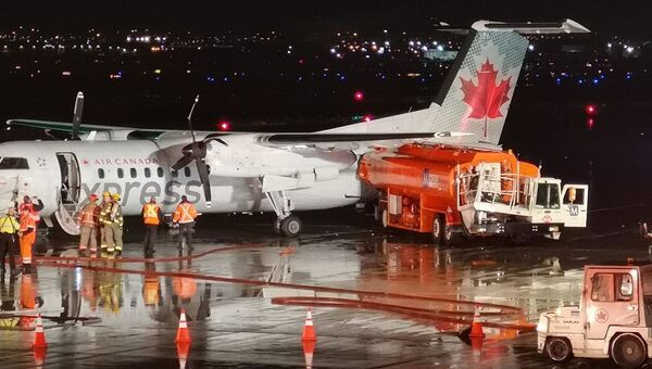 На месте столкновения самолета Air Canada Jazz и бензовоз в аэропорту Торонто, Канада