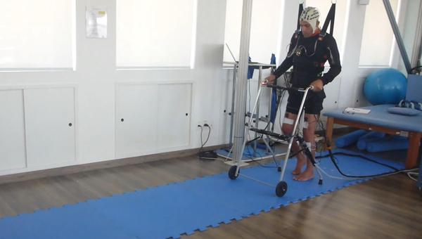 Доброволец учится ходить при помощи стимулятора спинного мозга и системы чтения мыслей