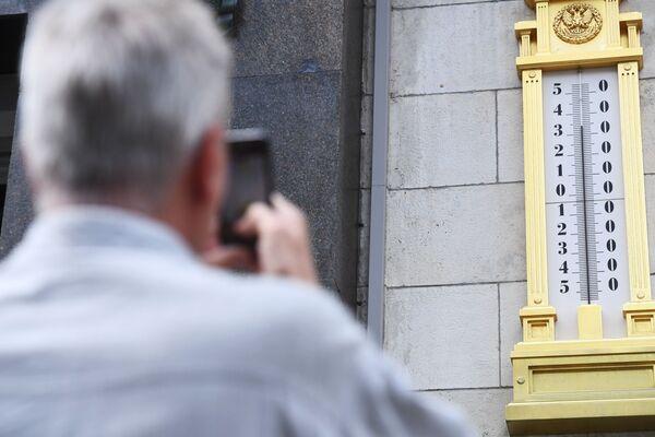 Мужчина фотографирует термометр
