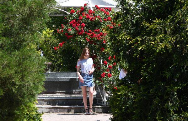 Девушка позирует возле фонтана в Ботаническом саду в Симферополе