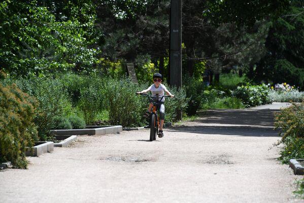 Ребенок катается на велосипеде в Ботаническом саду в Симферополе