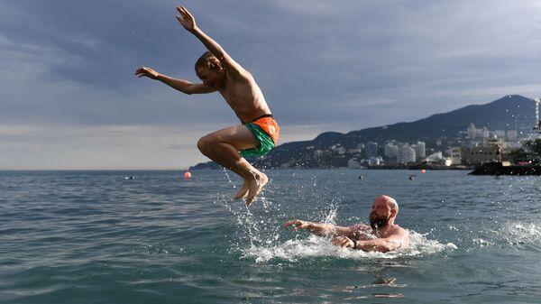 Отдыхающие купаются в Черном море в Ялте