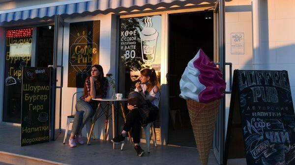 Девушки сидят за столиком в уличном кафе в Севастополе