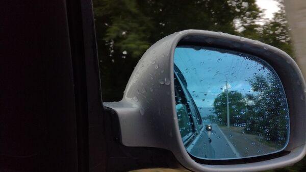 Дождь в отражении зеркала машины