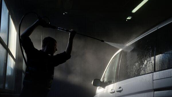 Мужчина моет машину на автомойке