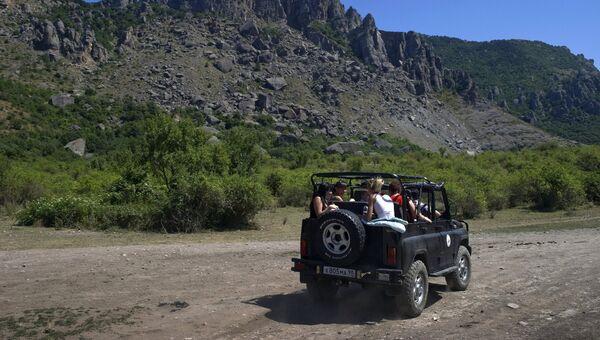 Туристы на экскурсии в джипе в окрестностях горы Демерджи в Крыму
