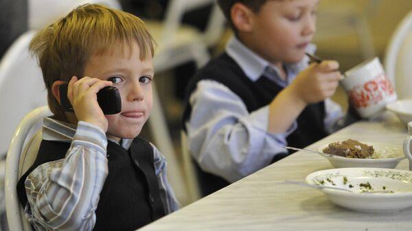 Ребенок с мобильным телефоном в школьной столовой. Архивное фото