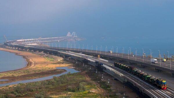 Рабочий состав с щебнем идет по железнодорожной части Крымского моста