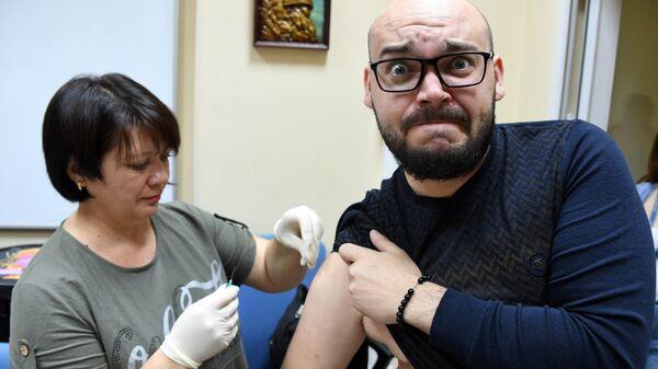 Медик делает прививку с вакциной против гриппа