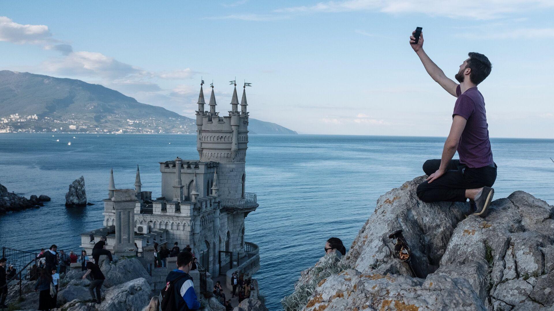 Туристы на береговой скале рядом с замком Ласточкино гнездо в поселке Гаспра в Крыму. - РИА Новости, 1920, 17.09.2020