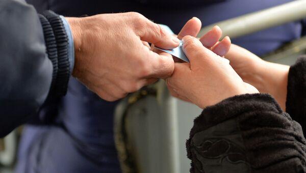 Контролер проверяет проездные документы у пассажиров